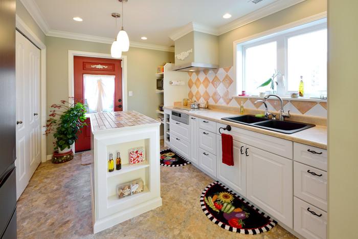 赤い勝手口のドアが印象的な輸入キッチンは、タイルやアクセントカラーで愉しさを演出。十分な広さを確保されていると同時にアイランドを設けることで、非常に勝手が良く使いやすい。