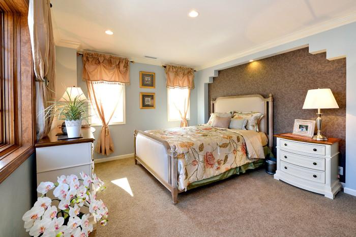 ベッド頭部側のニッチとモールディングが特徴のベッドルーム。家具やカーテン、インテリア小物に至るまでトータルコーディネイト